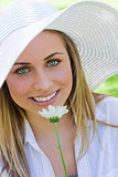 Young attractive blonde girl wearing a white hat while holding a