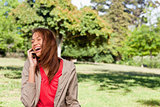 Young woman enthusiastically laughing while on the phone in an o