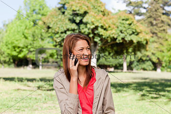 Young woman talking on the phone while looking toward the side i