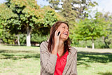 Woman laughing joyfully on a phone while standing in a sunny gra