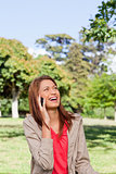 Woman laughing on the phone while looking towards the sun