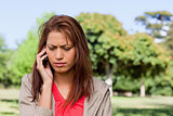 Woman looking towards the ground while on the phone in a bright