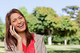 Young woman laughing happily on the phone in a bright park area