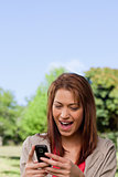 Woman with a happy expression reading a text message
