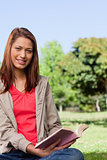 Woman happily holding a book while sitting in a bright park