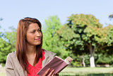 Woman smirking towards the side while reading a book
