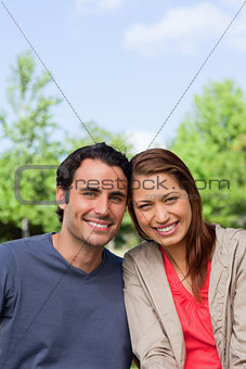 Two friends smiling as the look ahead while leaning against each