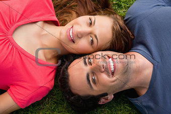 Two friends smiling while lying head to shoulder