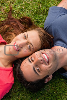Close-up of two friends smiling while lying head to shoulder