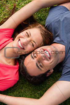Two friends smiling while lying head to shoulder with an arm out