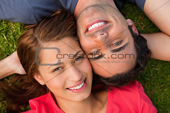 Close-up of two friends looking upwards while lying head to shou