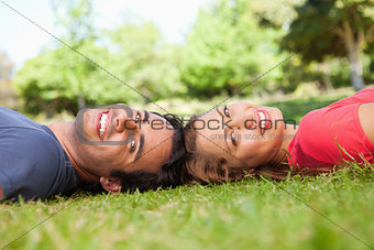 Two smiling friends looking towards the side while lying head to