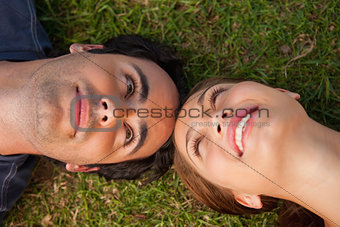 Close-up of two friends looking at each other while lying head t