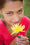 Woman looking upwards while holding a yellow flower