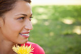 Woman looking towards the side while holding a yellow flower