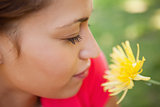 Woman closes her eyes as she smells a yellow flower