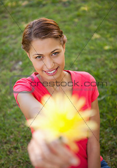 Woman holding a flower in one hand at arms reach