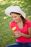 Woman wearing a white hat while holding a yellow flower