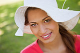 Woman smiling while wearing a white hat