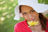 Woman wearing a white hat while smelling a yellow flower