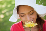 Woman wearing a white hat while smelling a flower with her eyes 