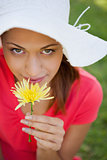 Woman wearing a white hat while smelling a flower while looking 