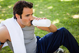 Man looking ahead while drinking from a sports bottle