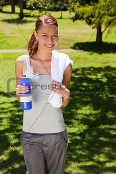 Woman smiling while holding a sports bottle and a towel