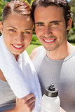Man holding a sports bottle with a woman holding a towel
