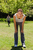 woman bending over while a man is running in the background