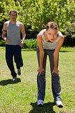 Woman bending over while a man is jogging in the background