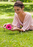 Woman lying on her front while holding a flower 