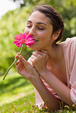 Woman smelling a flower while lying on her front