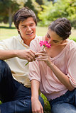 Woman smelling a flower which is being given to her by a man
