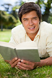 Man looking ahead while reading a book as he lies on grass