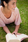 Woman looks to the side while reading a book as she is lying dow