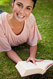 Smiling woman looking up while reading a book as she lies down
