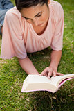 Woman looking down at a book while lying in grass