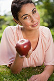 Woman offers an apple while lying in grass