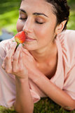 Woman smells an strawberry while lying in grass