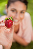 Woman holding a strawberry at arms reach