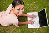 Woman looking upwards while using laptop