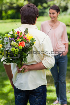 Man about to surprise his friend with a bouquet of flowers