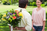 Man about to present a bouquet of flowers to his friend
