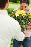 Woman smells flowers with are being given to her by a friend