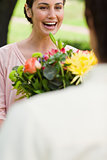 Woman laughing as she is being presented with flowers
