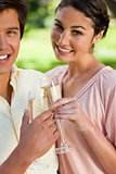 Woman smiling while touching glasses of champagne with her frien