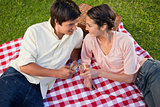 Two friends smiling towards each other during a picnic