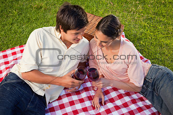 Two friends looking downwards while holding glasses of wine duri