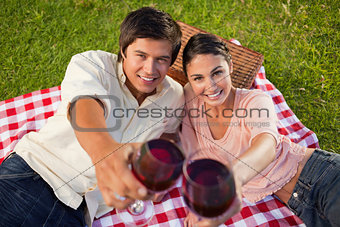 Two friends smiling as they touch their raised glasses during a